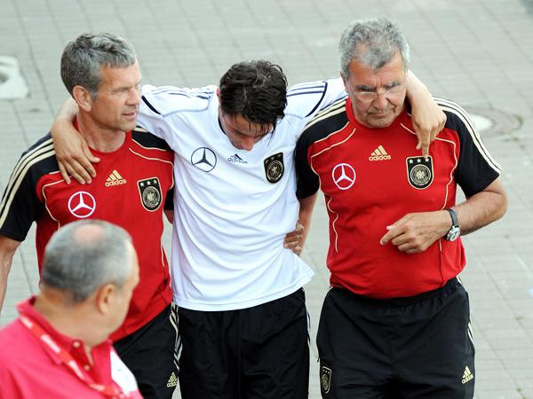 Verletzt: Christian Träsch humpelt gestützt von zwei Betreuern vom Platz.