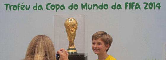 Schon jetzt ist die Vorfreude riesig: Ein Junge im Dress der Selecao lässt sich vor dem WM-Pokal ablichten.