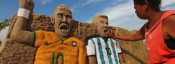 Sandfiguren von Neymar und Lionel Messi auf der Copacabana