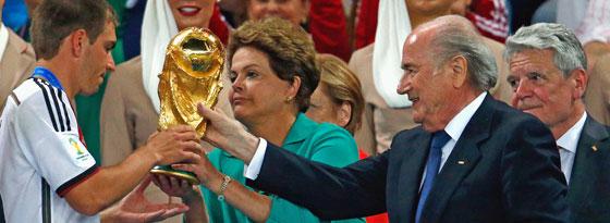 Philipp Lahm nimmt den Pokal von Brasiliens Staatspräsidentin Dilma Rousseff entgegen, daneben Sepp Blatter.