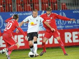 Dreikampf: Sandhausens Frank Löning wird von den Burghausern Christoph Behr (links) und Christian Burcia gedoppelt.