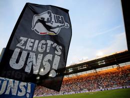 Das Drittliga-Logo auf einer Fahne vor Stadienkulisse