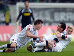 Von wegen am Boden: Havard Nordtveit und Marco Reus herzen Freistoßschütze Juan Arango.