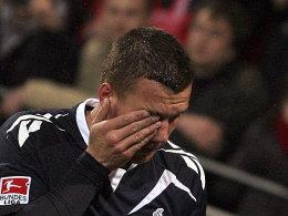 Lukas Podolski wurde von einer Münze unter dem Auge getroffen.