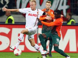 Augsburgs Kevin Vogt (li.) gegen Bremens Joseph Akpala