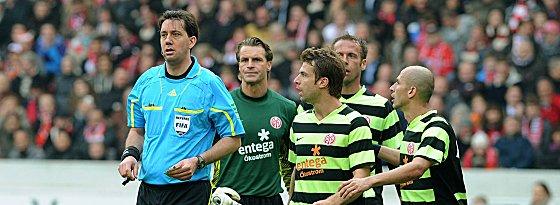 Mainzer Spieler reklamieren nach einer Entscheidung von Manuel Gräfe.