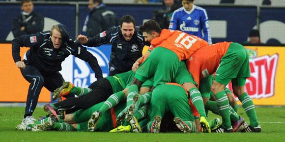 Fürths Trainer Mike Büskens (li.) wirft sich auf seine Spieler, die das 2:1 auf Schalke bejubeln.