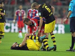 Mats Hummels krümmt sich vor Schmerzen, Mario Götze und Sven Bender erkundigen sich.