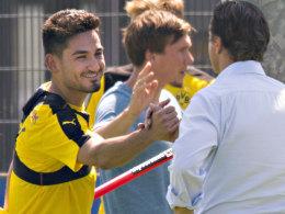 Ilkay Gündogan klatscht sich zum Trainingsauftakt mit Manager Michael Zorc ab.