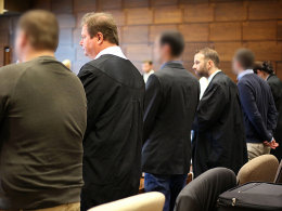 Die Angeklagten und ihre Rechtsanwälte am Dienstag vor dem Landgericht Köln