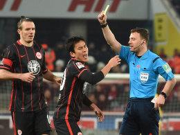 Schiedsrichter Felix Zwayer zieht Gelb, Frankfurts Makoto Hasebe will es nicht wahrhaben.