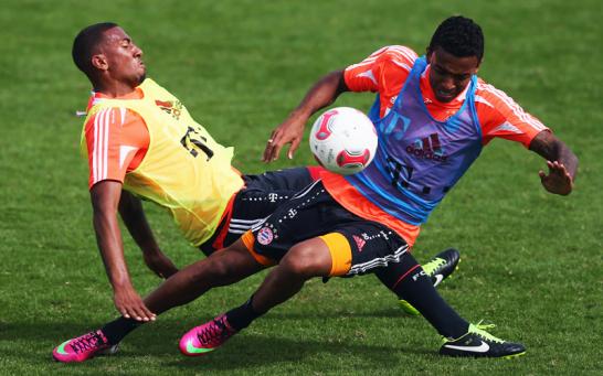Luiz Gustavo (vorne) kommt im Zweikampf mit Bayern-Teamkollege Jerome Botang in Doha zu Fall.