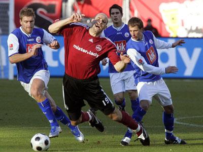 Rostocks Rahn (li.) und Rathgeb nehmen Nürnbergs Koller in die Zange