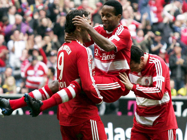 Zé Roberto herzt Toni, Sagnol schiebt von hinten an.