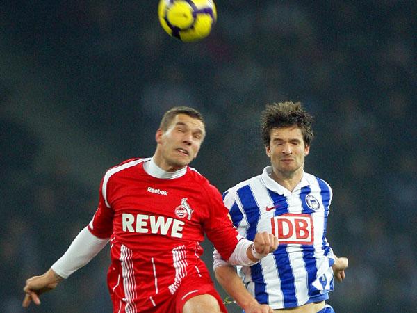 Lukas Podolski (li.) gegen Arne Friedrich.