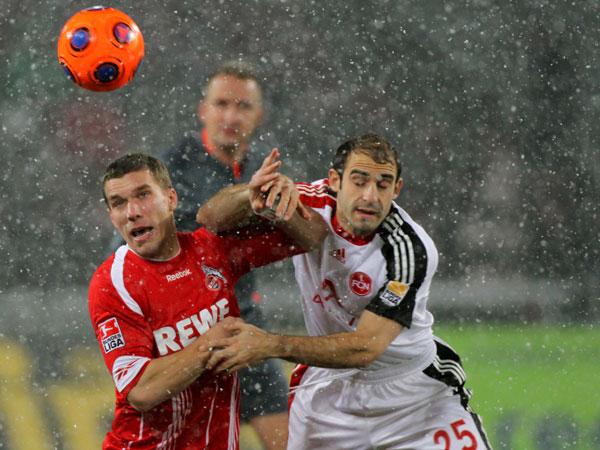 "Podolski (li.) und Pinola ""ringen"" um den Ball"