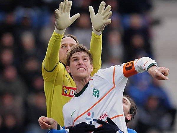 Fußball, Bundesliga: Per Mertesacker kommt nicht an Ball, weil Timo Hildebrand höher springt.