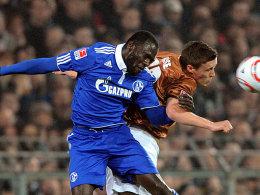 Schalkes Sarpei und St. Paulis Kruse in einem engen Kopfballduell.