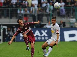 Stuttgarts Gentner spielt den Ball, Neustädter (re.) schaut nur hinterher