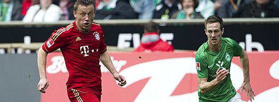 Bayerns Olic gegen Bremens Affolter (re.).