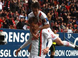 Augsburgs Kapitän Verhaegh springt vor Freude auf Langkamp, der soeben das 1:0 geköpft hat