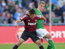 Bremens Petersen im Zweikampf mit Kiyotake (vorne)