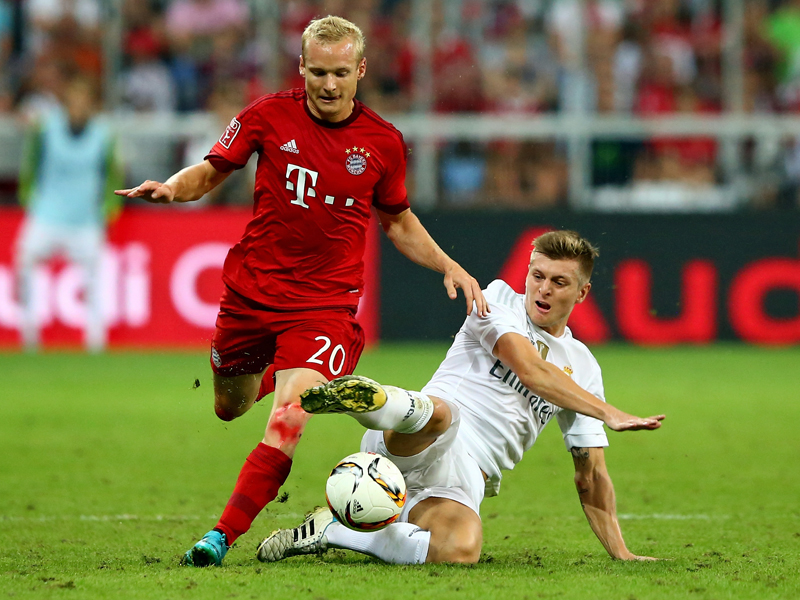 Toni Kroos erobert mit einer starken Grätsche gegen Bayerns Sebastian Rode den Ball.