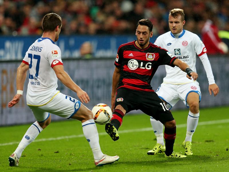 Leverkusens Hakan Calhanoglu wird von den Mainzern Christian Clemens (li.) und Daniel Brosinski gedoppelt.