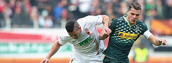 Mit Haken und Ösen: Augsburgs Raul Bobadilla im Duell mit Granit Xhaka (re.).