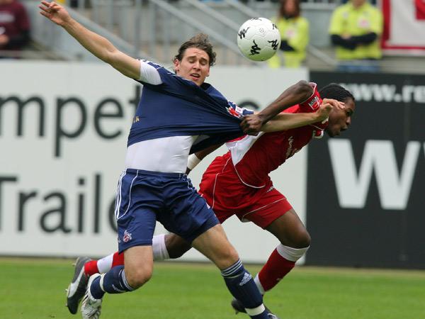 Lauterns Defensivspieler Mandjeck gegen Kölns Helmes (li.)
