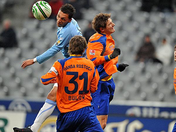 Münchens Holebas setzt sich hier wuchtig gegen zwei Rostocker durch.