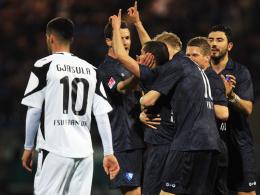 Gefühlslagen: Azaouagh (Arme oben) wird von seinen VfL-Kollegen gefeiert, während Frankfurts Gjasula den Kopf hängen lässt.