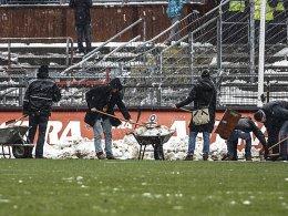 Freiwillige halfen vor der Partie, den Rasen in Hamburg vom Schnee zu befreien.