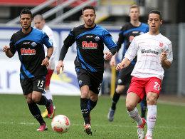 Den Ball im Blick: Paderborns Kachunga und Naki setzen dem Regensburger Machado nach.