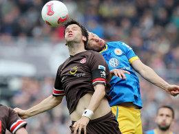 St. Paulis Bruns im Kopfballduell gegen Pfitzner (re.).