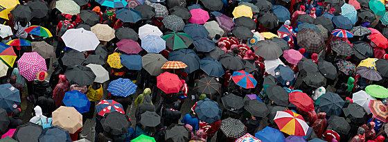 Die Fans harren aus: Der Marienplatz füllt sich und Regenschirme dominieren.
