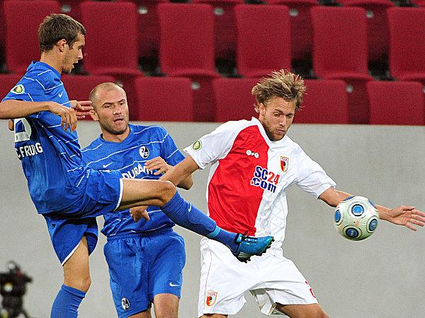 Fußball, DFB-Pokal: Julian Schuster (l.) und Ivica Banovic (SC Freiburg) gegen Daniel Brinkmann (FC Augsburg)