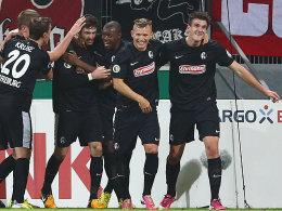 Matchwinner: Daniel Caligiuri wird von seinen Freiburger Teamkollegen geherzt.