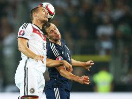 Intensives Duell: Lukas Podolski im Zweikampf mit Schottlands Steven Whittaker (re.).