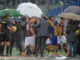 Nichts geht mehr in Rom: Totti wird bei starkem Regen vom Feld geleitet.