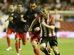 Duell der deutschen EL-Konkurrenten: Atleticos Arda Turan jagt Bilbaos Iker Muniain (re.).