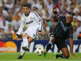 Cristiano Ronaldo schießt, Kompany (re.) kommt zu spät