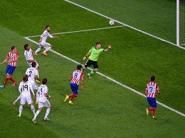 Diego Godin (li.) bringt Atletico per Kopf in Führung. Real-Schlussmann Casillas sieht dabei nicht gut aus.