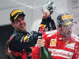 Überschäumende Freude: Indien-Sieger Sebastian Vettel duscht den zweitplatzierten Fernando Alonso mit Champagner.