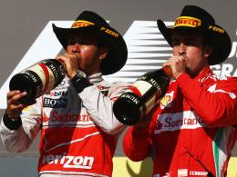 Gut behütet: Sieger Lewis Hamilton (li.) und der drittplatzierte Fernando Alonso bei der Siegerehrung nach dem Premierenrennen.