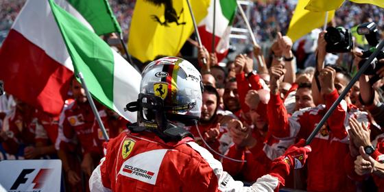 Roter Jubel: Sebastian Vettel schwenkt vor der Ferrari-Crew die italienische und die Ferrari-Fahne.
