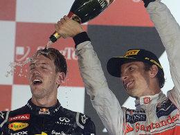 Abkühlung in der Sauna Singapur: Jenson Button verpasst Sieger Sebastian Vettel die gebührende Dusche.