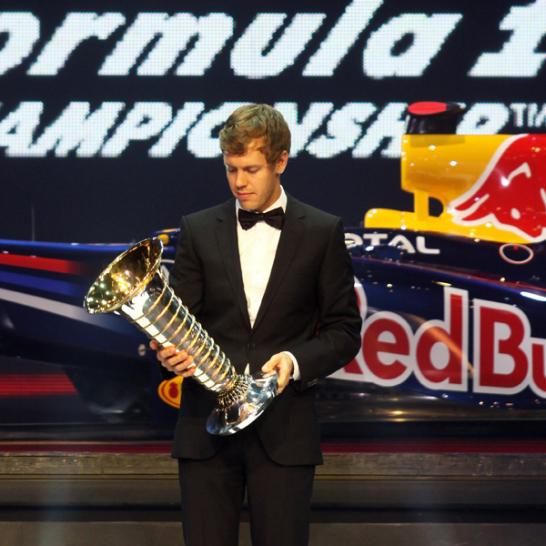 Sebastian Vettel hat zum zweiten Mal in Folge den Weltmeisterpokal �berreicht bekommen. Und sieht ihn beinahe ungl�ubig an.