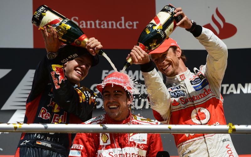 Ein glücklich grinsender Alonso lässt sich nach der Siegerehrung von Vettel und Button mit Champagner duschen.