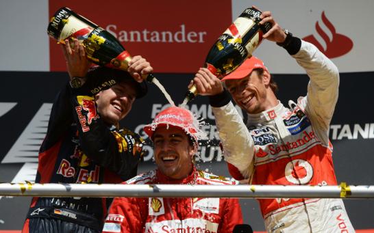 Ein gl�cklich grinsender Alonso l�sst sich nach der Siegerehrung von Vettel und Button mit Champagner duschen.